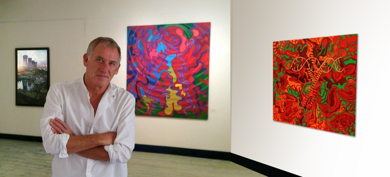 Denis Taylor Artist with paintings at a recent exhibition